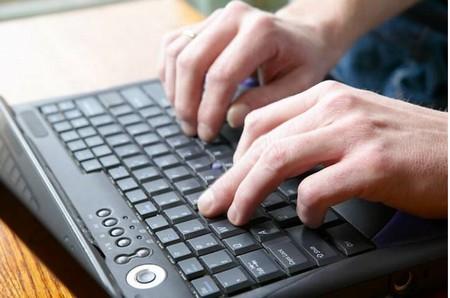 Si vedono la tastiera di un pc e le mani di un redattore on line