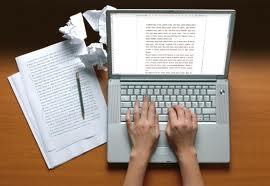 Un pc acceso, due mani sulla tastiera e intorno dei fogli di carta appallottolati