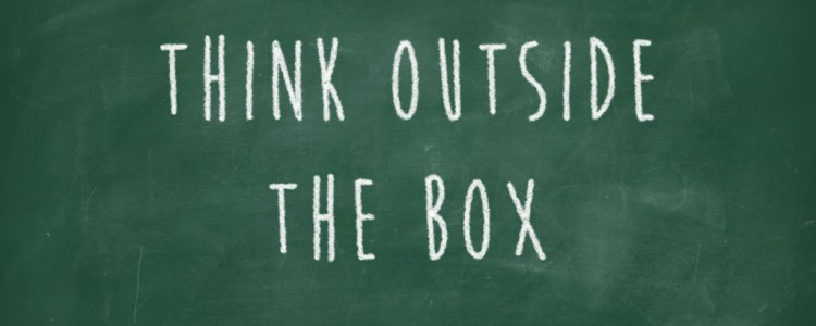 Think outside the box handwritten on blackboard