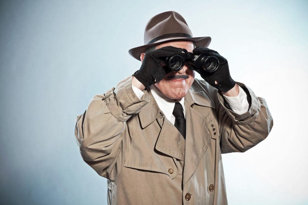 Vintage detective with mustache and hat. Looking through binoculars. Studio shot.